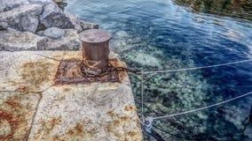 Sluit omhoog mening van geroeste meerpaal op de rand van de kust stock foto's