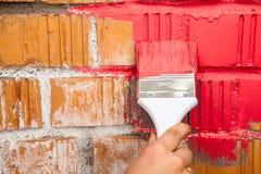 Sluit omhoog mening van hand met verfborstel in rode kleur Royalty-vrije Stock Foto