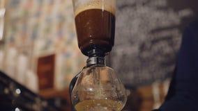 Sluit omhoog mening van het brouwen van koffie in een alternatief koffiezetapparaat in 4K stock videobeelden