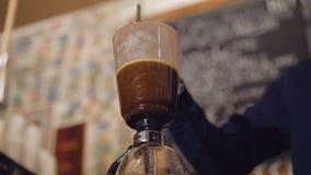 Sluit omhoog mening van het brouwen van koffie in een alternatief koffiezetapparaat in 4K stock footage