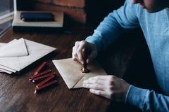 Sluit omhoog mening van het gebruiken van zegelwas op de envelop zegel royalty-vrije stock afbeeldingen