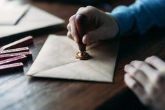 Sluit omhoog mening van het gebruiken van zegelwas op de envelop zegel stock foto's