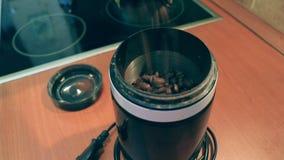 Sluit omhoog mening van het gieten van koffiebonen in de molen stock video