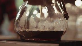 Sluit omhoog mening van het gieten van hete gebrouwen koffie, bezoeker van de koffie op de achtergrond Binnen het schieten Koffie stock video