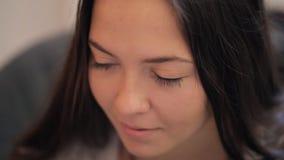 Sluit omhoog mening van het jonge vrouw zitting en glimlachen stock footage