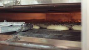 Sluit omhoog mening van het plaatsen van ongebakken broodbroden in de oven door mannelijke handen Voorbereidend gezond voedsel, p stock video