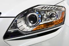 Sluit omhoog mening van koplamp witte auto Stock Foto