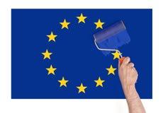 Sluit omhoog mening van man& x27; s hand het schilderen over ster op de Unie van Europa vlag Stock Foto's