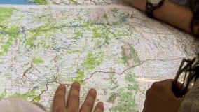 Sluit omhoog mening van mens en vrouw die op plaatsen op wereldkaart de richten stock afbeelding