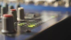 Sluit omhoog mening van mixer soundboard met knoppen en opvlammende groen lichtindicatoren in moderne opnamestudio Langzame Motie stock videobeelden