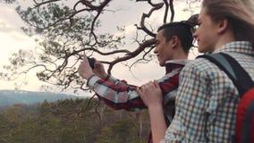 Sluit omhoog mening van modieus paar op de bovenkant van de rots die foto's nemen, controlerend de geschotene foto's Jong en mooi stock video