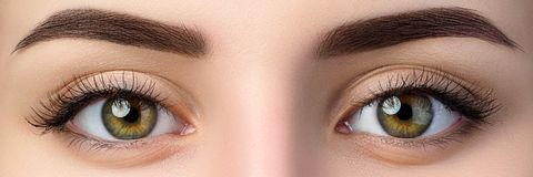 Sluit omhoog mening van mooie bruine vrouwelijke ogen royalty-vrije stock afbeelding