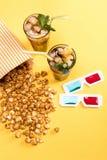Sluit omhoog mening van popcorn, bevroren thee en 3D glases op geel Royalty-vrije Stock Foto's