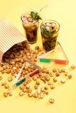 Sluit omhoog mening van popcorn, bevroren thee en 3D glases op geel Stock Afbeelding