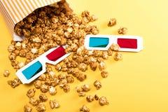 Sluit omhoog mening van popcorn en 3D glazen op geel Stock Afbeeldingen