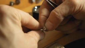 Sluit omhoog mening van puttin de halfedelsteen in een oud wijf van metaalring in juwelen langzame motie stock video