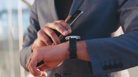 Sluit omhoog mening van sterke man'shand met luxueuze toebehoren controlerend tijd die via slim horloge, het bevorderen in held stock footage