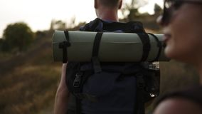 Sluit omhoog mening van twee wandelaars, vrienden of paar die actieve vrije tijd hebben Trekking met rugzakken door heuvel met dr stock video