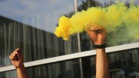 Sluit omhoog mening van vlotter van de mensen de golvende rook van verzadigde gele kleur stock videobeelden