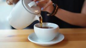 Sluit omhoog mening van vrouwelijke handen die hete thee van de theepot in de witte porseleinkop gieten op de houten lijst in kof stock footage