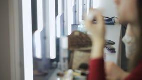 Sluit omhoog mening van vrouwen die kosmetische hulpmiddelen in zak zetten stock video