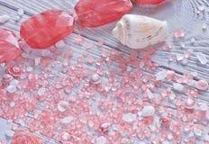 Sluit omhoog mening van zeeschelpen, aromatherapy zout en koraalhalsband Tedere achtergrond Stock Afbeelding