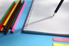 Sluit omhoog meningsnotitieboekjes, kleurrijke potloden, op een blauwe achtergrond Terug naar het Concept van de School Vlak leg stock foto