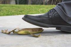 Sluit omhoog, Mens die met zwarte leerschoen, op banaanschil stappen stock afbeeldingen