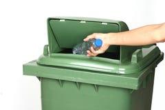 Sluit omhoog mensenhand weg werpend plastic fles in het recycling van bak Stock Foto
