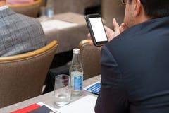 Sluit omhoog mensenhanden die en mobiele telefoon houden met behulp van op vergadering stock foto's