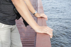 Sluit omhoog mensenkou uit op houten brug bij rivieroever Royalty-vrije Stock Afbeelding