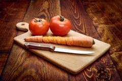 Sluit omhoog mes en tomaat op houten lijst Stock Afbeelding