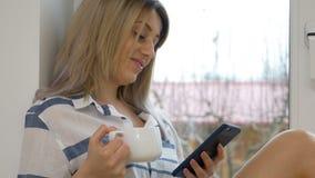 Sluit omhoog met sexy vrouw die slimme telefoon en koffiezitting houden door het venster stock videobeelden
