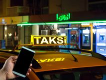 Sluit omhoog mobiele telefoon op hand en taxiautoachtergrond stock foto's