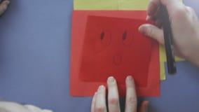 Sluit omhoog moeder en de handen die van de dochter potlood houden die een verbaasd gezicht trekken op papier, spelen samen thuis stock videobeelden