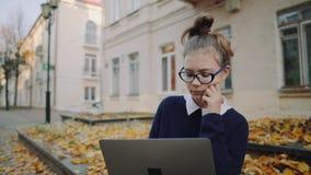 Sluit omhoog mooie het meisjeszitting van de hipstertiener op een stoep op de straat van de de herfststad en werkende laptop comp stock video
