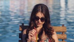 Sluit omhoog Mooie jonge vrouw die bikini het drinken cocktail dragen, het zitten door de pool en het zonnebaden stock footage