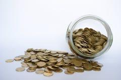 Sluit omhoog muntstukken in glaskruik op witte lijst Rond verspreide muntstukken Geïsoleerdj op witte achtergrond Een kruik van d stock foto