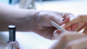 Sluit omhoog nagellak een nagelvijl stock video