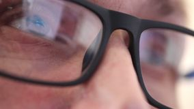 Sluit omhoog ogen van een mens met glazen die zorgvuldig de monitor of de werkende apparaten bekijkt stock videobeelden