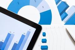 Sluit omhoog ontsproten van bedrijfstablet en diagrammen Stock Fotografie