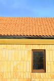 Sluit omhoog onvolledig dak Dakhuis met betegeld dak op blauwe hemel marmeren tegel op de muur in een nieuw venster Onvolledig da Stock Afbeeldingen