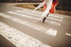 Sluit omhoog op de benen van de vrouw op de weg Het lopen van de vrouw royalty-vrije stock afbeelding
