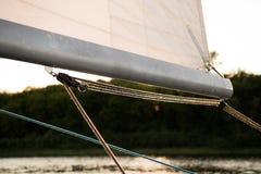 Sluit omhoog op de boommast van een varend jacht, met zeil en het monteren van kabels, en rivier of meerkust op de achtergrond royalty-vrije stock afbeeldingen