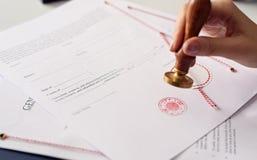 Sluit omhoog op de inkt van de de notarishand van de vrouw stempelend het document stock fotografie