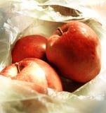 Sluit omhoog op drie rode appelen liggend in een transparante dunne plastic zak royalty-vrije stock fotografie
