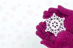 Sluit omhoog op handen die roze handschoenen dragen houdend een grote sneeuwvlok Stock Fotografie