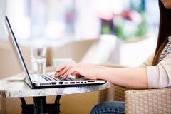 Sluit omhoog op handen van vrouw die werkend aan laptop terwijl openlucht zitten stock fotografie