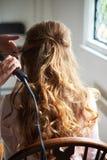 Sluit omhoog op het kapsel van het bruidhuwelijk met elektrische haarkrulspeld stock foto's