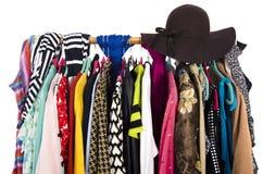 Sluit omhoog op kleurrijke kleren en hoed op hangers in een opslag Royalty-vrije Stock Afbeelding